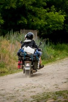 バイクに乗って、国で旅行するカップル。旅行、冒険、夏のコンセプト。バイクに乗るカップル