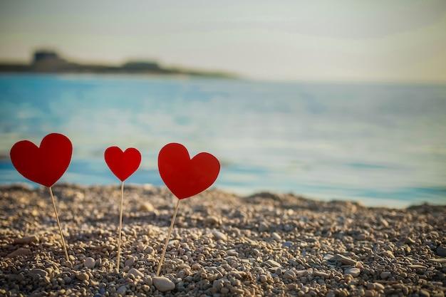 Романтический символ двух сердец на пляже. любовь. красное сердце на закате море. концепция я люблю тебя. день святого валентина. сердца на пляже стоят на палочках