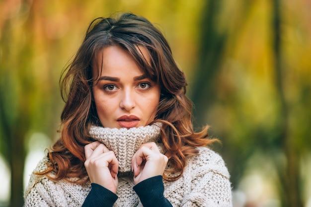 Очаровательная женщина с макияжем касается руками вязаного воротника и смотрит прямо в камеру