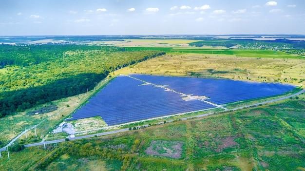 Панели солнечных батарей в птичьего полета. солнечная электростанция в поле. солнечная ферма. источник экологической возобновляемой энергии.