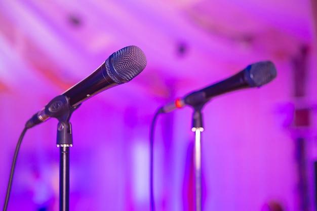 Два микрофона на стойках. микрофон на сцене. микрофон крупным планом. паб. бар. ресторан. классическая музыка. вечер. ночное шоу. европейский ресторан.
