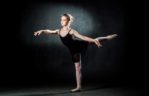 Красивая молодая балерина позирует и танцы в студии на темной стене. маленькая танцовщица.