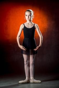 Красивая молодая балерина танцует в студии на темной стене. маленькая танцовщица. балерина.