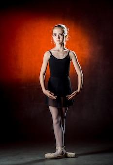 Балет. красивая молодая балерина позирует и танцы в студии на темной стене. маленькая танцовщица.