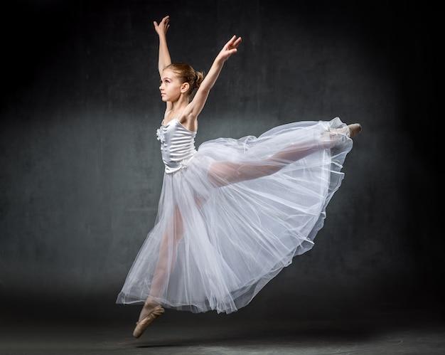 Балерина. милая маленькая девочка позирует и танцы в студии. девушка изучает балет.