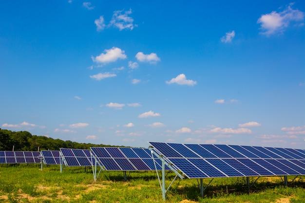 Синие солнечные батареи. электростанция. солнечная ферма. фотоэлектрические системы питания. панель солнечных батарей на фоне неба.
