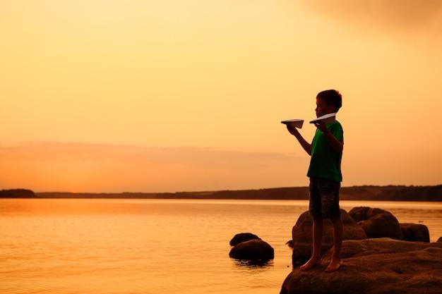 川の背景に紙飛行機で遊んで幸せな子。美しい夏の夕日。屋外の子供たちとのクラス。ライフスタイル