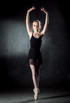 若いバレリーナのポーズとスタジオでダンス