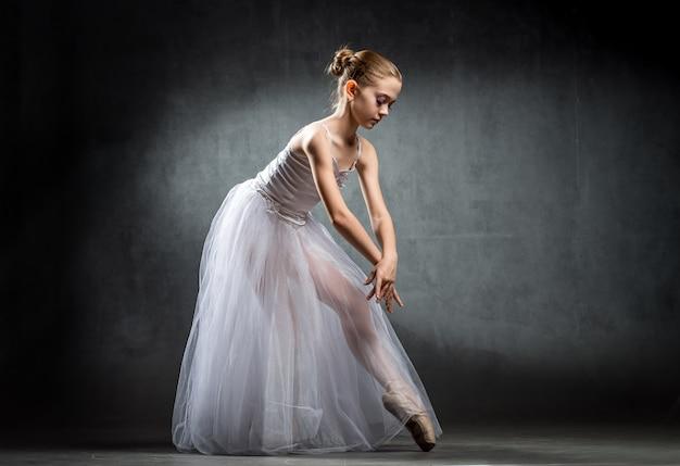 スタジオで踊る柔軟なかわいいバレリーナ