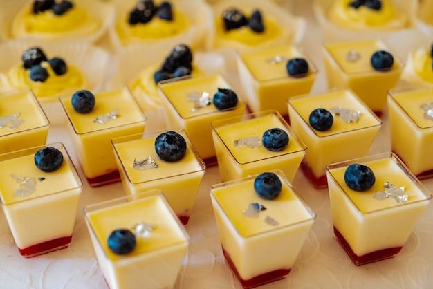 ビルベリーで飾られたゼリーとクリームのおいしいカラフルなパナコッタのフォームがテーブルにあります