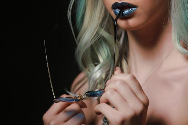 Лицо женщины с голубыми губами и очки в руках. молодая модель студии позирует. гламурный макияж