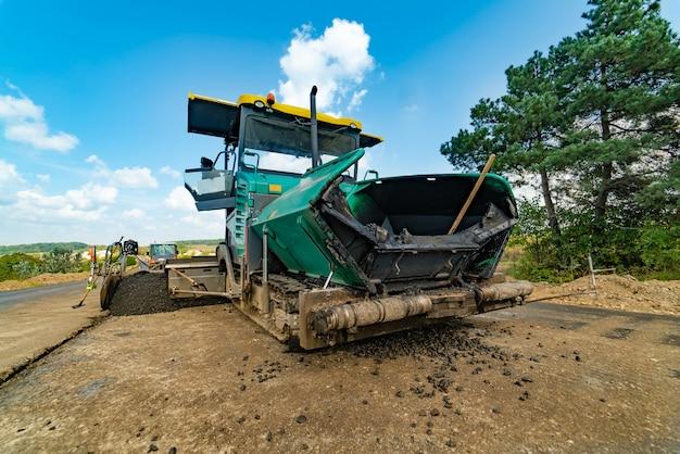 Профессиональная техника для выравнивания грунта находится на обочине дороги летом возле деревьев.