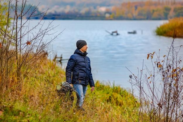 観光客は彼の手でバックパックを保持し、川の土手で高い草で遠くを見ます