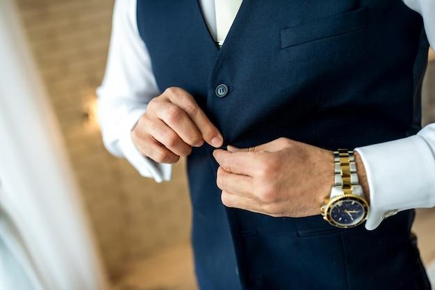 ビジネスの男性は彼のジャケットをボタンします。仕事の準備をしている男。