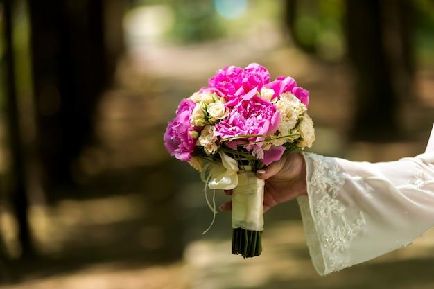結婚式。緑豊かな庭園に立って、花束を持ってドレスを着た花嫁