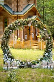 結婚式のアーチ。布の花と緑で装飾されています。松林の中にあります。