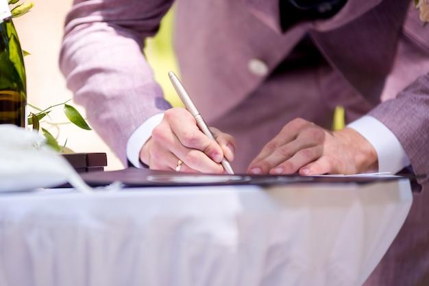 新郎が結婚許可証に署名します。署名式。結婚式の伝統。