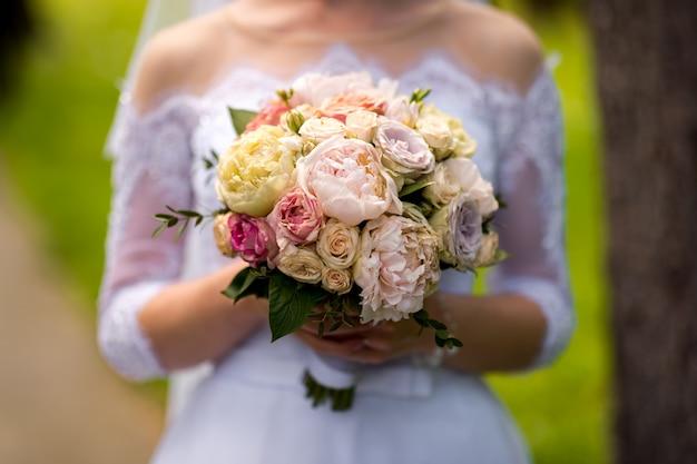 緑豊かな庭園に立って、花と緑のウェディングブーケを持ってドレスの花嫁