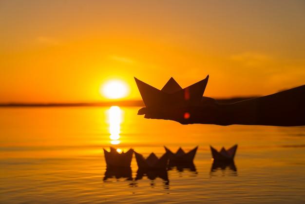 Бумажный кораблик на ладони мальчика. четыре бумажных оригами, которые плавают в реке на закате