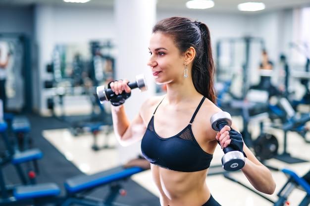 ジムでダンベルの筋肉を行使する女性。