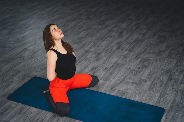 女性はジムでヨガを練習します。スポーツと健康的なライフスタイル。