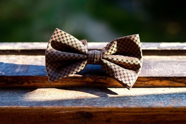 木製の背景に蝶ネクタイ。クラシックグルーミングアクセサリー