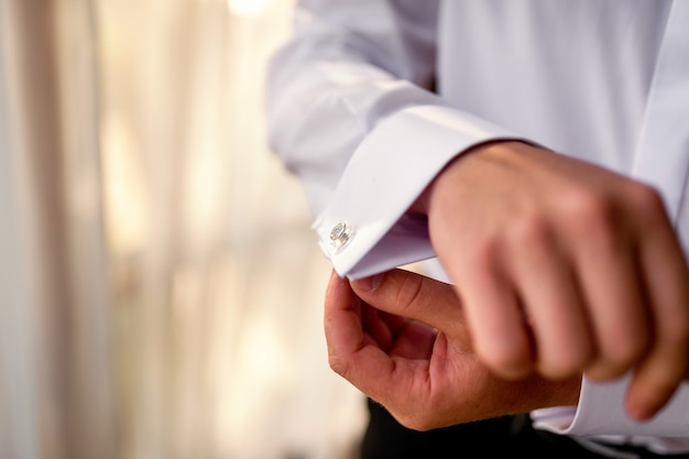 ビジネスマンはカフスボタンをつけます。結婚式前の朝に準備をする新郎