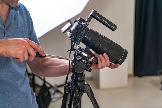 写真家の男がスタジオでの作業のためにプロのカメラを調整します