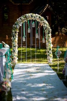 Арка для свадебной церемонии. украшен цветами и зеленью. находится в сосновом лесу. молодожены. свадебный декор.