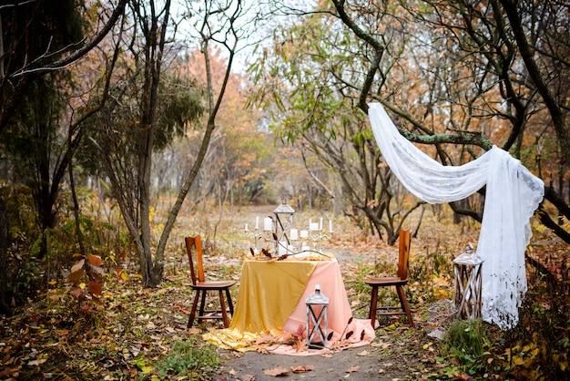 Стол с осенним декором накрыт на двоих в лесу. осенняя свадьба. свадебный декор
