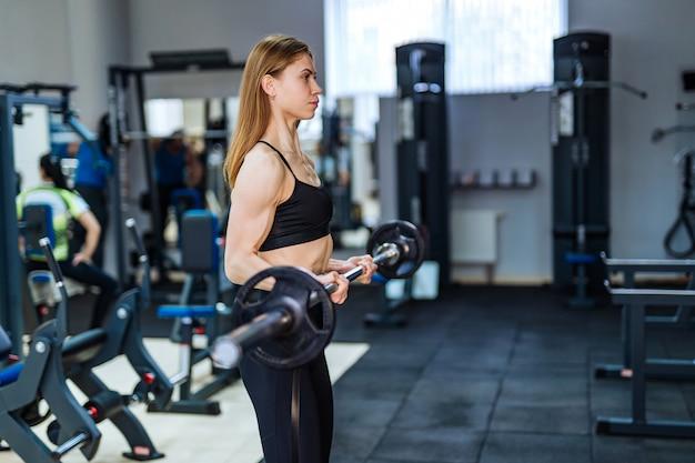 金属製のバーベルを持ち上げる完璧なボディを持つ運動少女。健康的なライフスタイルのコンセプト。