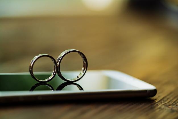 Два золотых кольца на телефоне в комнате. кольца в виде восьми бесконечных