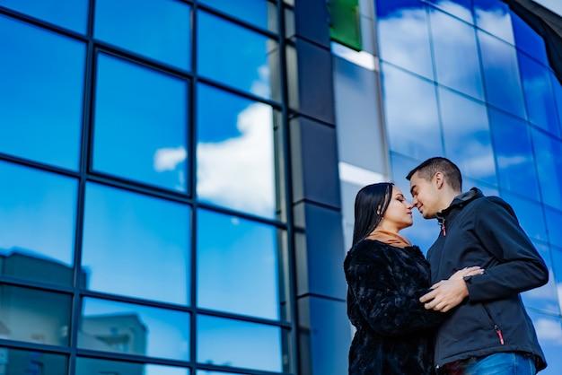 Влюбленная пара обнимает небоскреб с зеркальными окнами