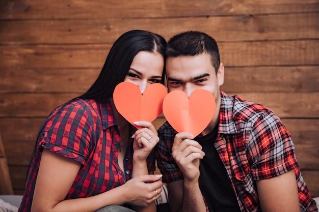 Влюбленная пара закрывает свои лица бумажными сердечками в день святого валентина.