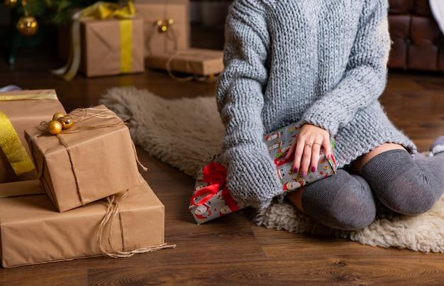 Женщина в вязаном сером платье сидит на ковре и держит в руках подарок в канун рождества