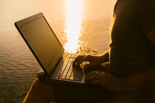 男の手はノートパソコンのキーボードで入力しています