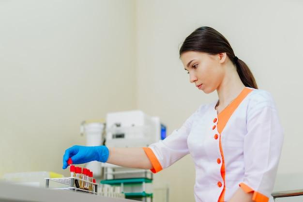 医療制服を着た美しい検査技師女性は、血液サンプルで動作します。