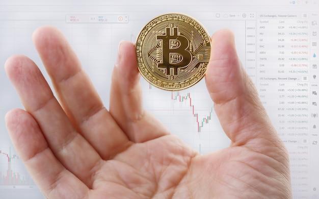 男の手は、コインの形でビットコインを保持しています