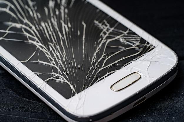 Смартфон с разбитым экраном. крупный план.