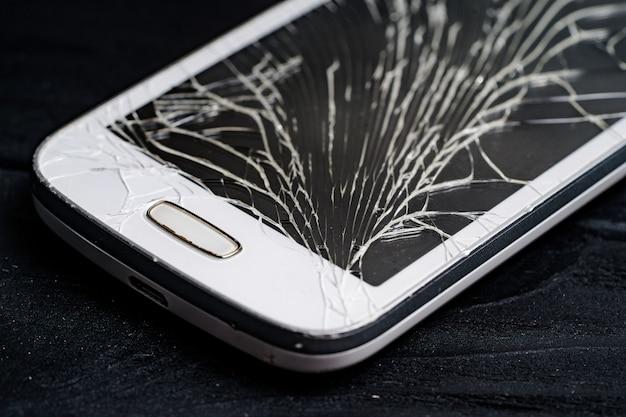 壊れた画面を持つスマートフォン。閉じる。