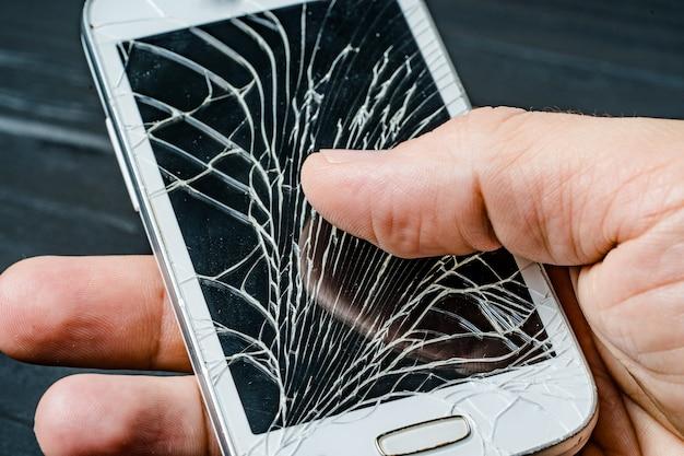 手に壊れた携帯電話の画面。割れたスマートフォンのガラス