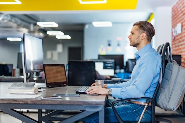 ソフトウェア開発会社のオフィスで多くのモニターを備えたデスクトップコンピューターで作業する男性プログラマー。ウェブサイトの設計プログラミングおよびコーディング技術。