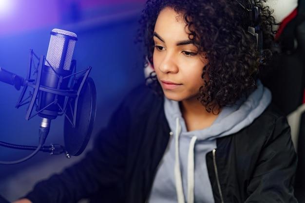 プロの少女ゲーマーは、彼女のコンピューターでビデオゲームをプレイします。彼女は、オンラインサイバーゲームトーナメント、自宅でのプレイ、またはインターネットカフェに参加しています。彼女はゲーミングヘッドセットを着ています