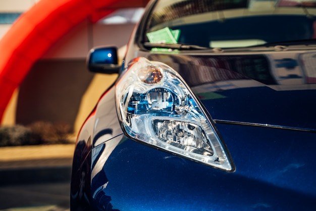 電気自動車のヘッドライト。ハイブリッドカー-ショールームでの新型車のプレゼンテーション