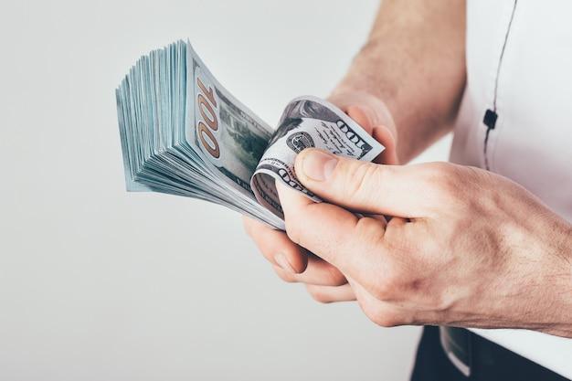 ビジネスマンは彼の手にお金を保持し、彼の収入を数えます。お金はドル札で積み重ねられている