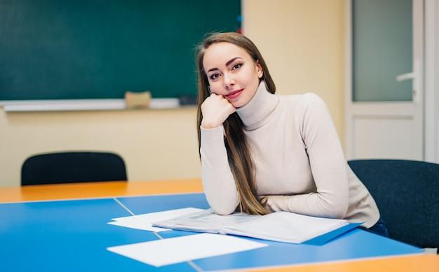 教室に座っている美しい学校の先生