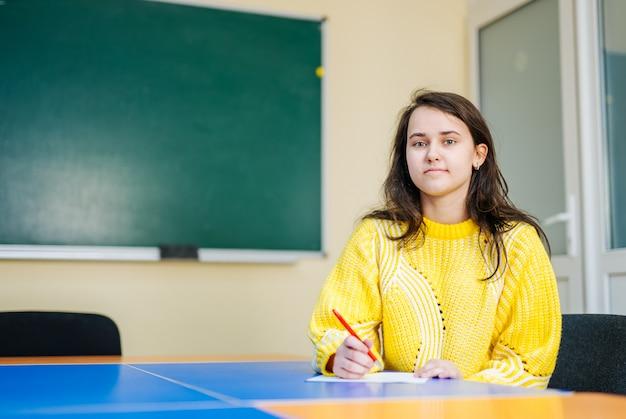 Портрет прекрасной девушки, глядя на камеру с улыбкой в классе