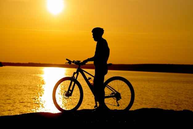 川の近くの日没でヘルメットを持つ男性サイクリストのシルエット