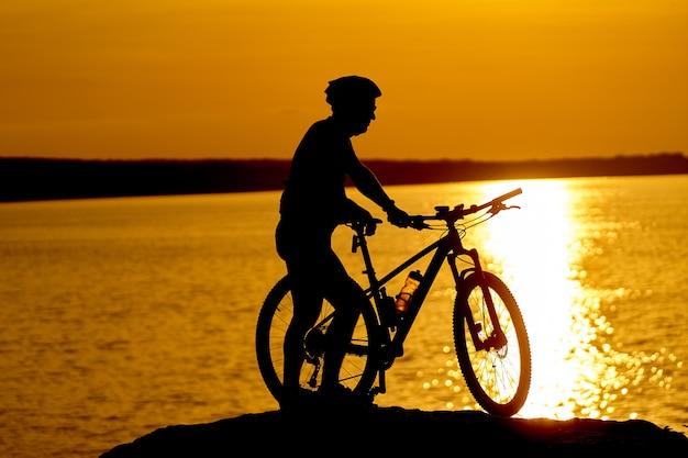 夕暮れの夏のビーチでサイクリング男