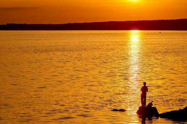 Рыбак на пирсе во время заката